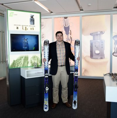 Clint Boyd is pictured with a display of the medical device he developed for K2M  and a pair of  custom skis, designed with spines, that he made for K2M's chief executive officer.